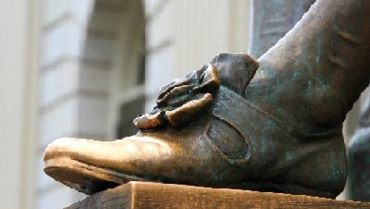 bronze statue of John Harvard -- image shows only his shiny shoe from where visitors and students rub it for good luck